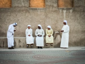 Arab men wearing traditional Arabic clothes sat on a wall in Bur Dubai