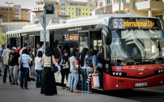 Immigrant workers boarding a bus to International City in Dubai