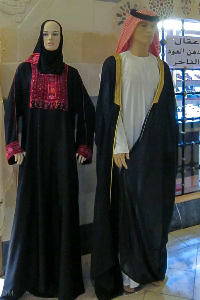 Female dummy wearing abaya and shayla. Male dummy wearing kandora, ghutra, agal, and bisht. Taken at Khan Murjan souk in Dubai.