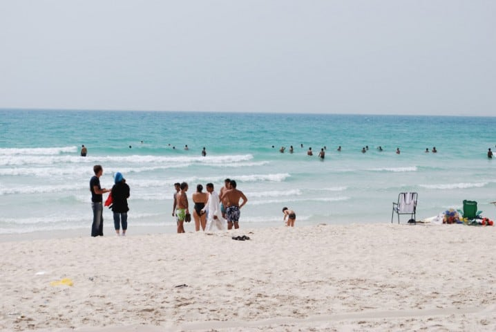 People walking and sunbathing on Jumeirah Beach Park in Dubai